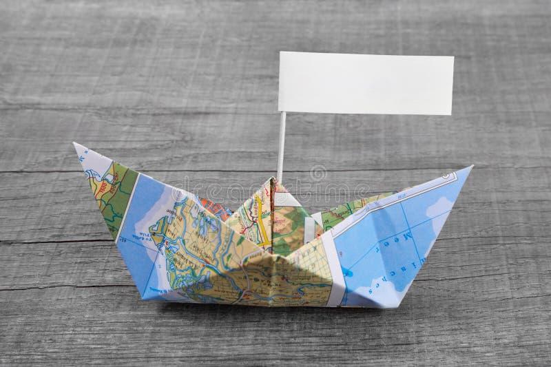 纸小船折叠了在与暂停标志的一张地图外面在灰色w 库存图片