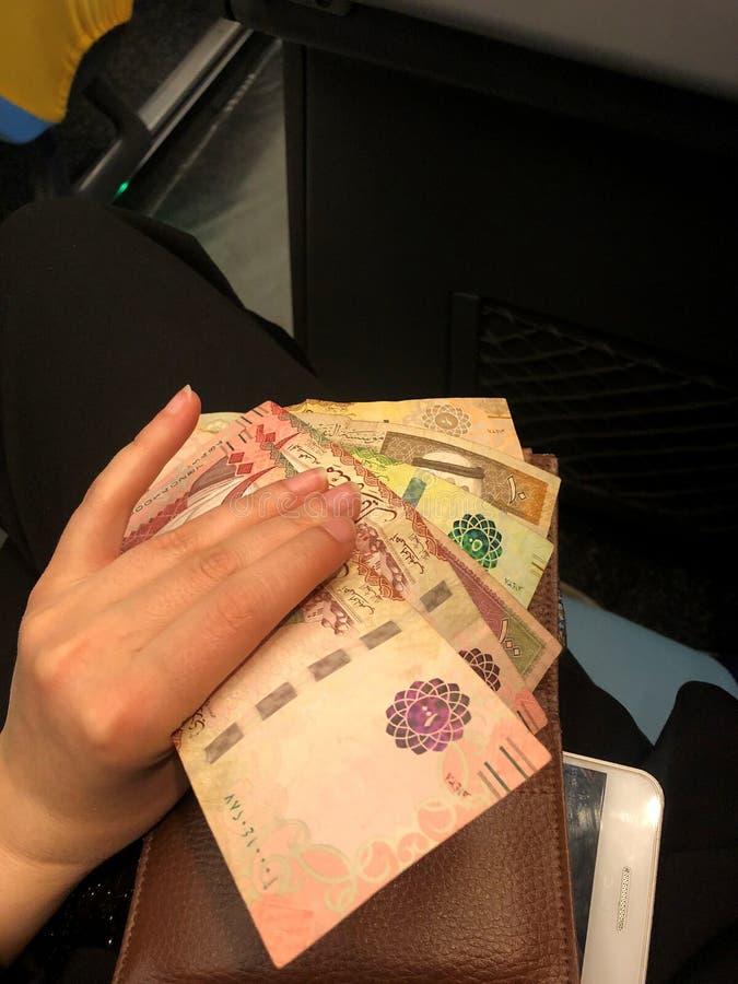 纸币在少女的手上 沙特阿拉伯的钞票 免版税库存照片