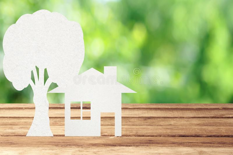 纸房子和树在木桌上与庭院bokeh室外t 免版税图库摄影