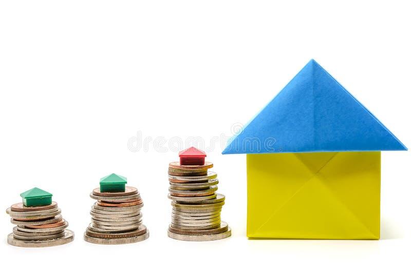 纸房子origami和微型家庭模型在金钱硬币在白色 免版税库存图片