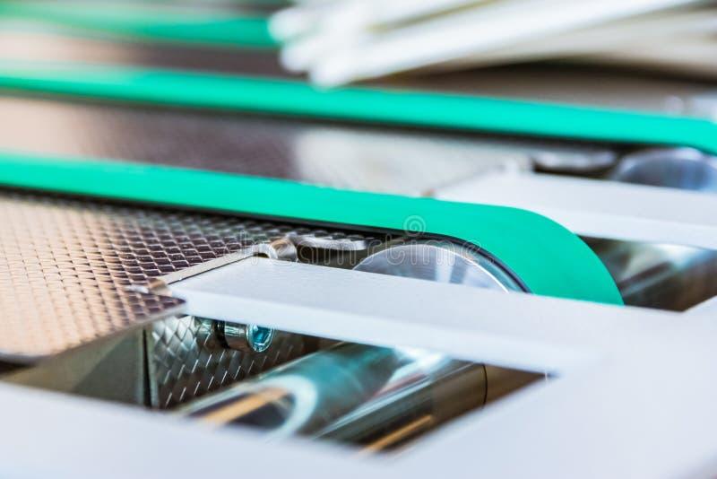 纸折叠的机器传送带橡胶稀薄的线绿色  免版税库存照片