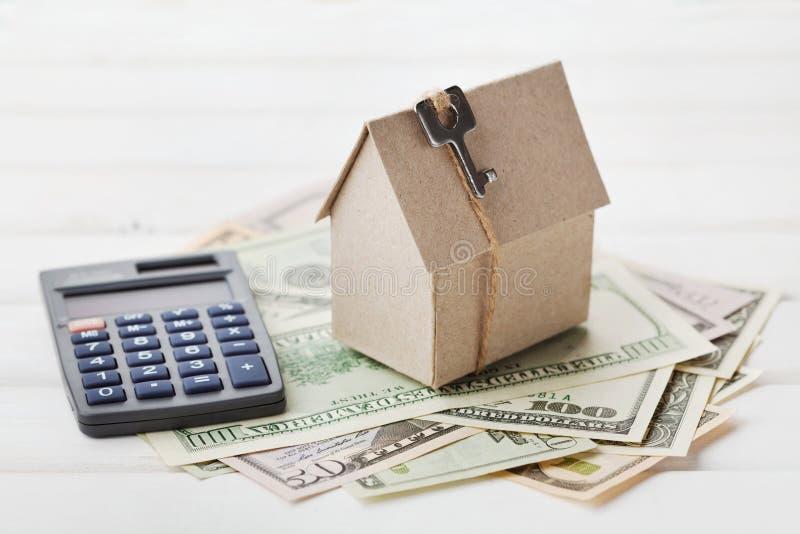 纸板房子模型有钥匙的,计算器和现金美元 房屋建设,贷款,房地产 公用事业的费用 免版税库存图片