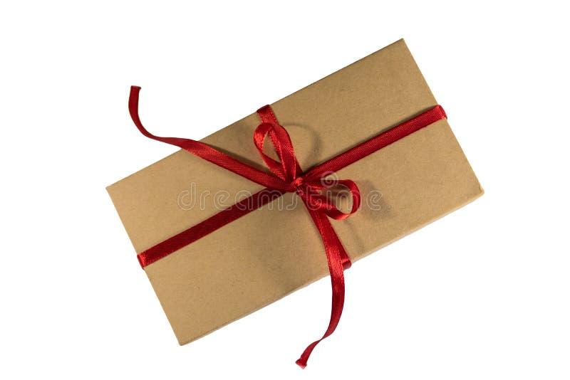 纸板有在白色背景隔绝的红色丝带的礼物盒 库存照片