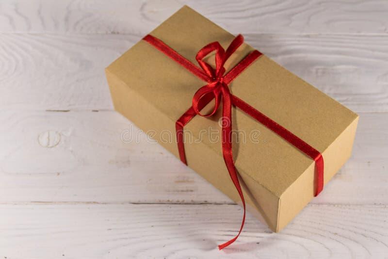 纸板有红色丝带的礼物盒在白色木桌上 免版税库存图片