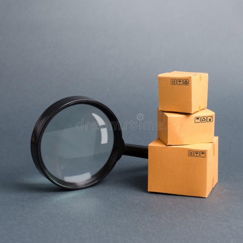 纸板箱和放大镜 完成品和设备仓库  买卖商品和服务 免版税图库摄影
