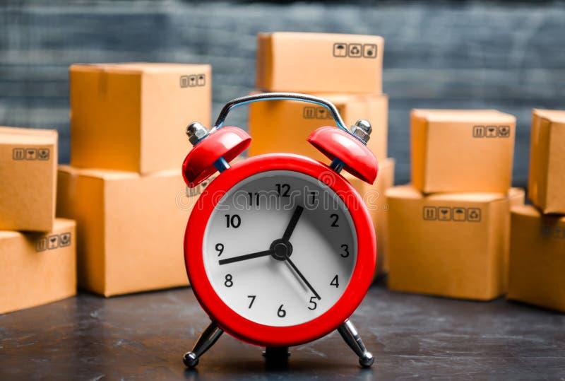 纸板箱和红色闹钟 交货时间 有限的供应,在股票、炒作和消费者热病的物品短缺 时间 免版税库存图片