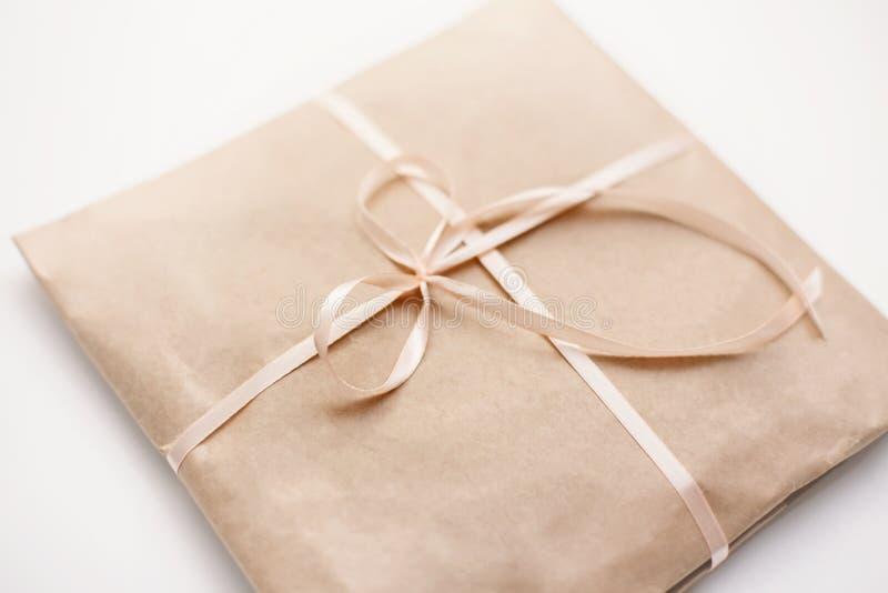 纸板纸盒包裹包裹与浅褐色的纸和栓与在弓的桃红色串丝带 库存照片
