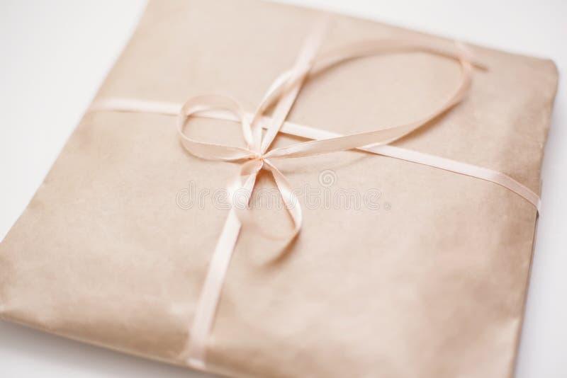 纸板纸盒包裹包裹与浅褐色的纸和栓与在弓的桃红色串丝带 库存图片