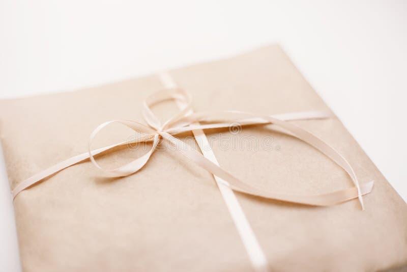 纸板纸盒包裹包裹与浅褐色的纸和栓与在弓的桃红色串丝带 免版税库存图片