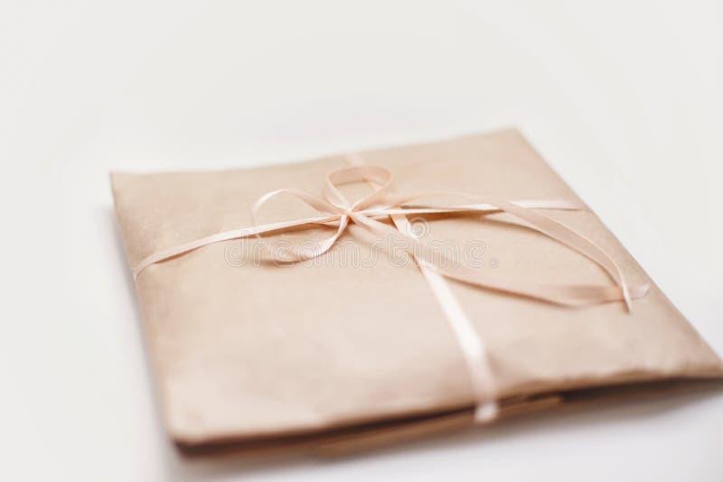 纸板纸盒包裹包裹与浅褐色的纸和栓与在弓的桃红色串丝带 免版税库存照片