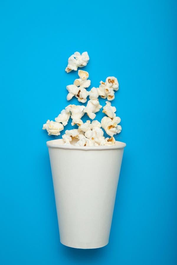 纸桶或一个杯子用玉米花在蓝色背景,假装 免版税库存照片