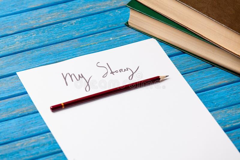 纸照片我的故事和堆在美妙的蓝色的书 库存照片