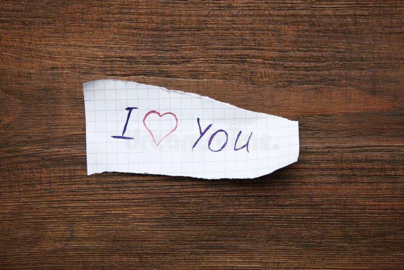 纸片与词我爱你的在木桌上 免版税库存图片