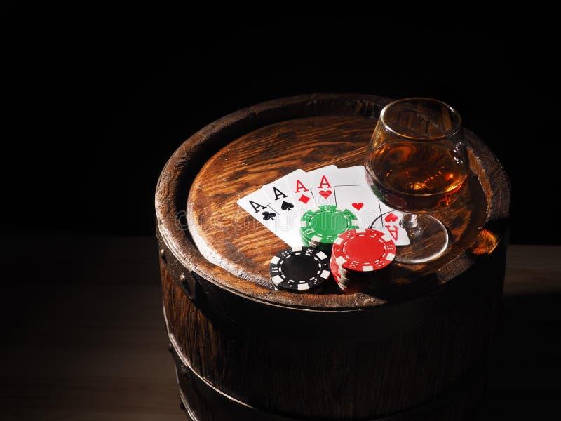 纸牌和科涅克白兰地酒杯在桶的 库存图片