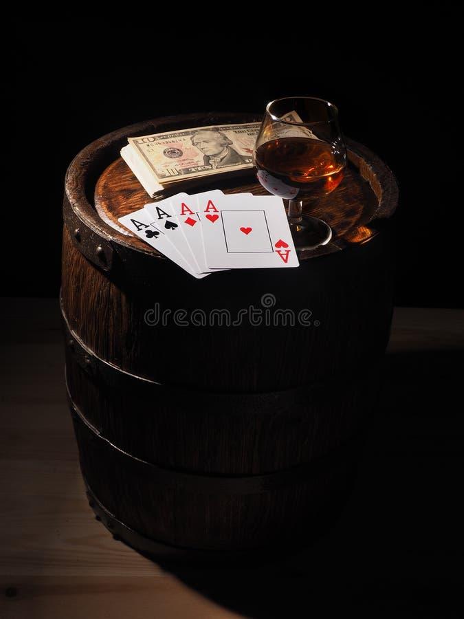 纸牌和科涅克白兰地酒杯在桶的 免版税库存照片