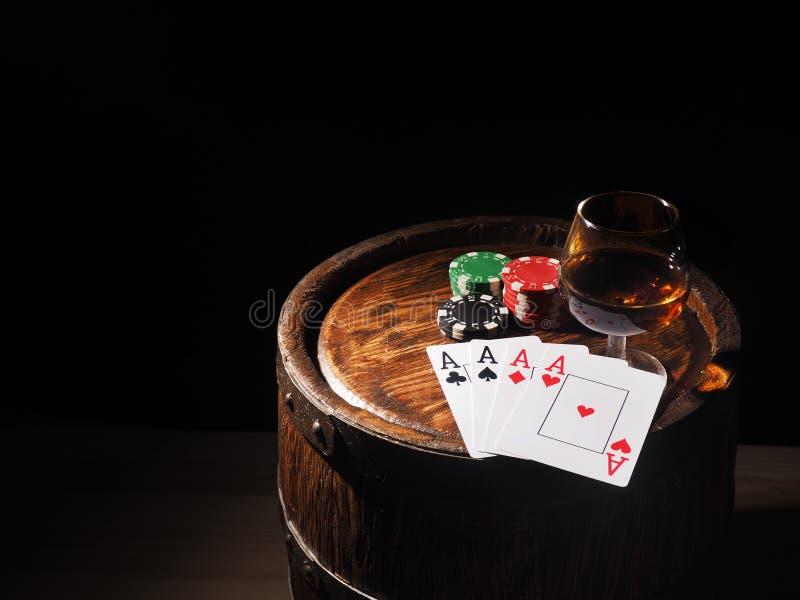 纸牌和科涅克白兰地酒杯在桶的 图库摄影