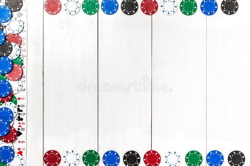 纸牌和纸牌筹码在白色木背景 顶视图 免版税库存照片