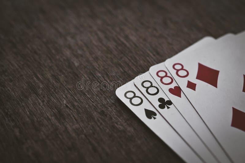 纸牌四在一张木桌上的eights特写镜头 库存照片