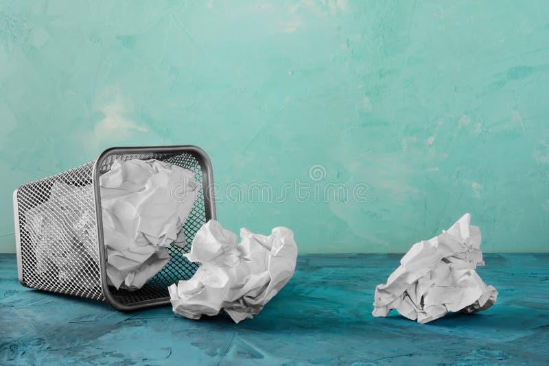 纸的一个下落的垃圾箱 疏散纸团 与地方的美好的绿松石背景文本的 空的框 库存图片