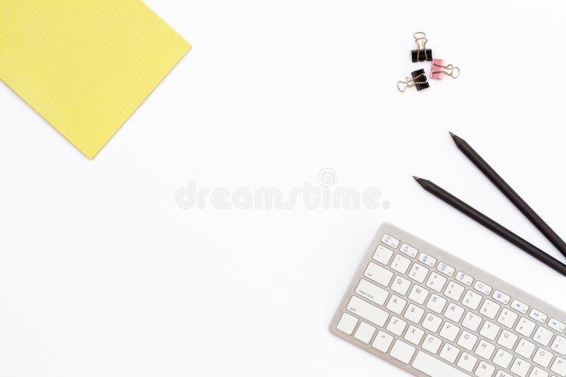 纸的黄色笔记薄,键盘,两黑铅笔和夹子在白色背景 桌面的最小的概念在的  图库摄影