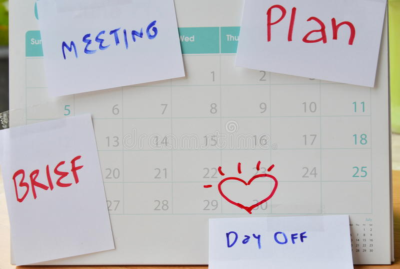纸笔记为假期提醒在日历的棍子 图库摄影