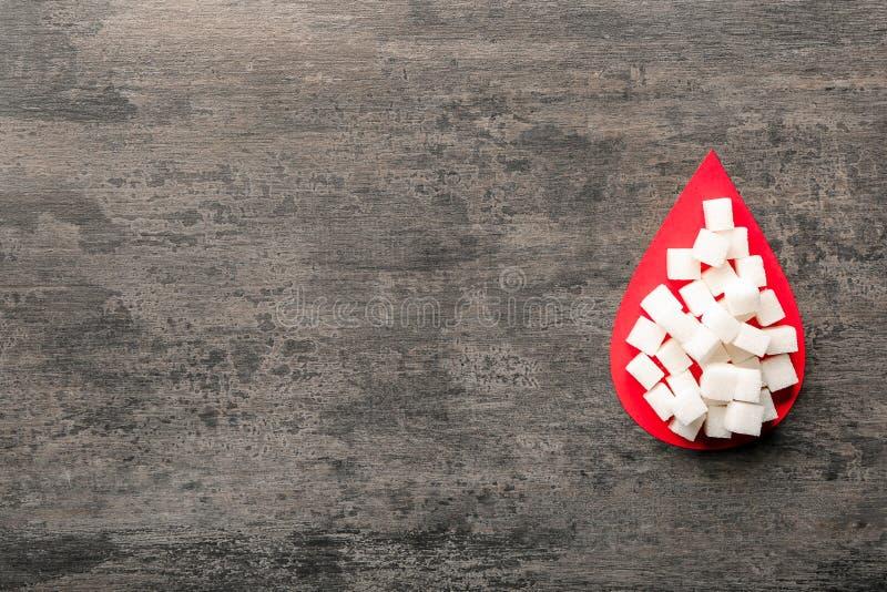 纸血液下落和糖立方体在木桌上 r 免版税图库摄影