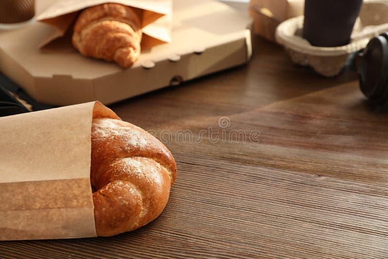 纸袋用酥皮点心和外卖食品在桌上 文本的空间 库存图片