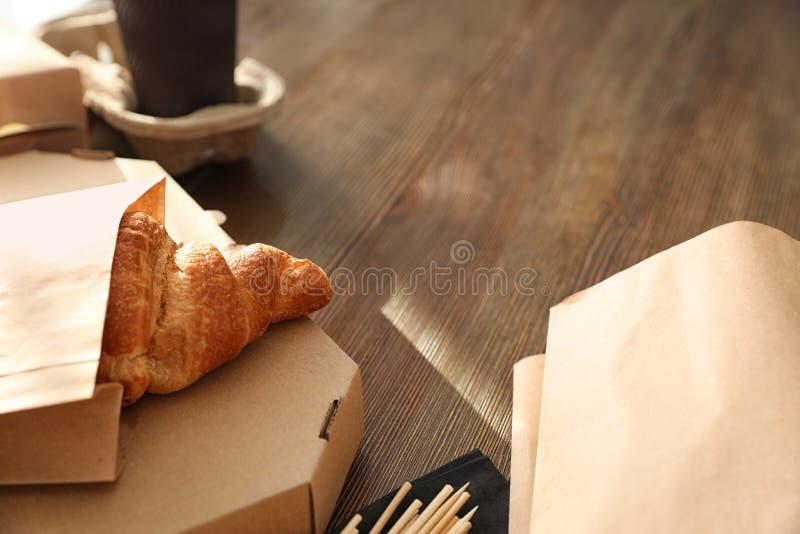 纸袋用酥皮点心和外卖食品在桌上 文本的空间 图库摄影
