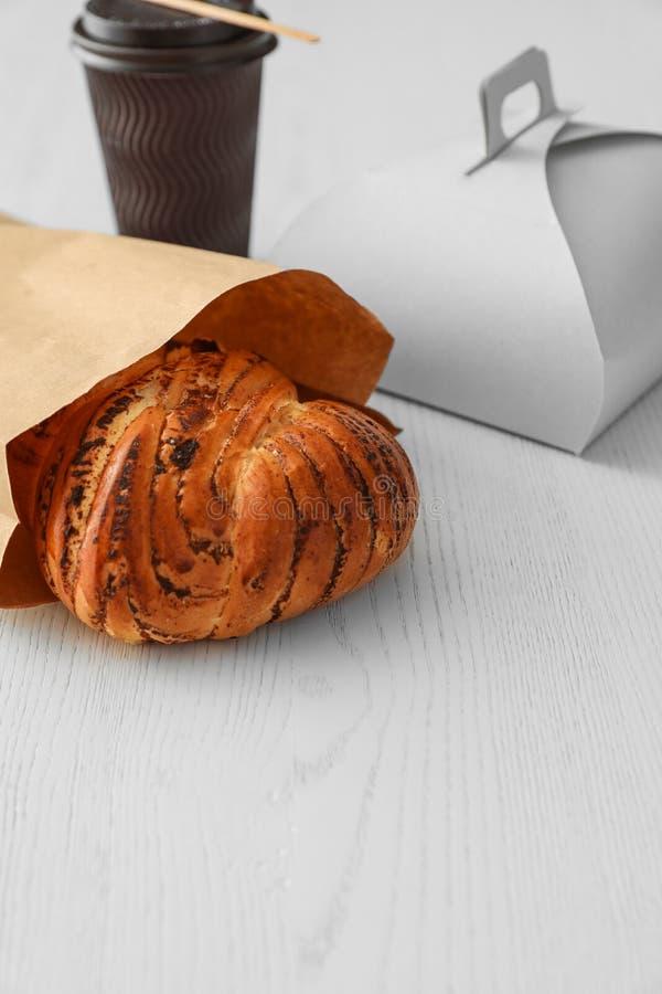 纸袋用酥皮点心和外卖食品在桌上 r 库存照片