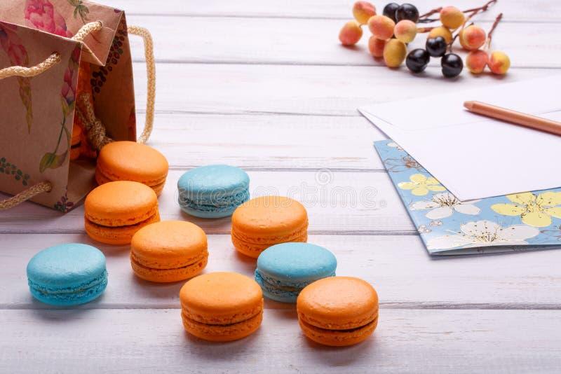 纸袋用饼干colorfool蛋白杏仁饼干和明信片与铅笔和信封 在白色木bac的可口法国点心 图库摄影