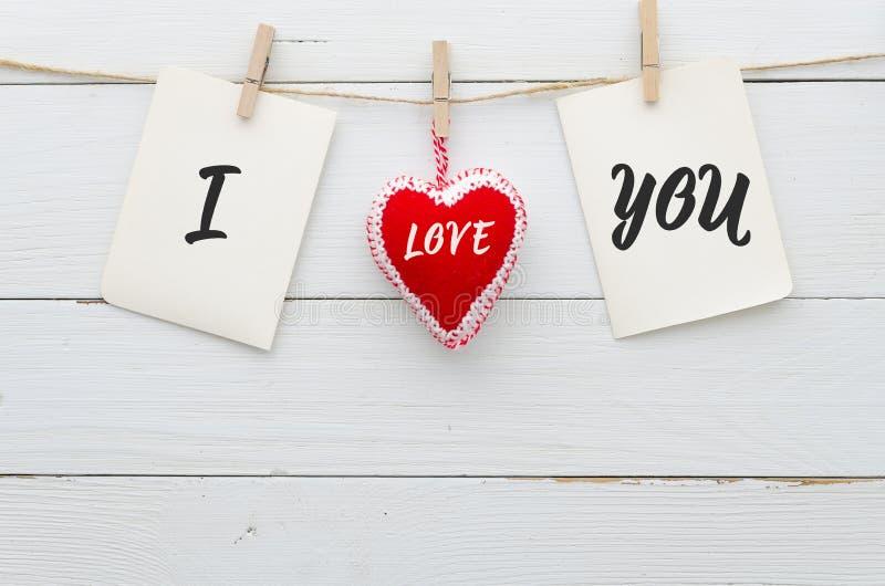 纸贴纸附有与在绳索的晒衣夹和感觉心脏在白色木板条背景做词我爱你 库存图片