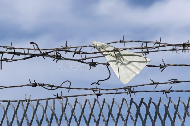 纸飞机陷在铁丝网 库存图片