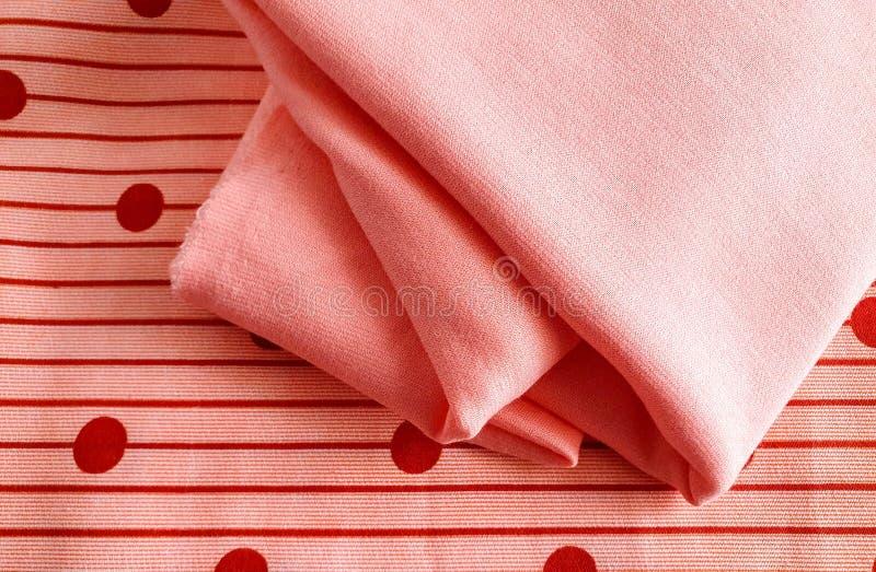 纹理、背景、样式、灰棕色或者橙色棉花与带红色小点与软的桃子颜色棉花结合 这种织品能 免版税库存图片