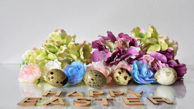 纺织品花,鹌鹑蛋和在白色背景的复活节快乐上写字 免版税图库摄影