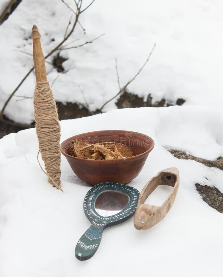 纺锤、镜子和黏土板材用在雪的面包 仍然lif 库存照片