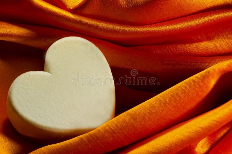 纺织品在橙色satine布料的心脏箱子 免版税库存照片