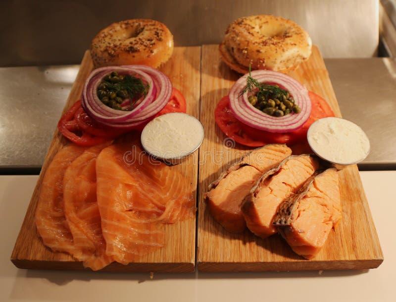 纽约与熏制和被烘烤的三文鱼的样式百吉卷在木板用乳脂干酪、蕃茄、葱和雀跃 免版税库存图片