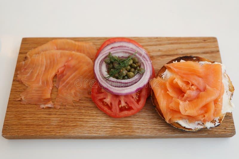 纽约与熏制鲑鱼的样式百吉卷在木板用乳脂干酪、蕃茄、葱和雀跃 免版税库存照片
