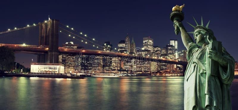 纽约地平线在与自由女神像的晚上 免版税库存照片