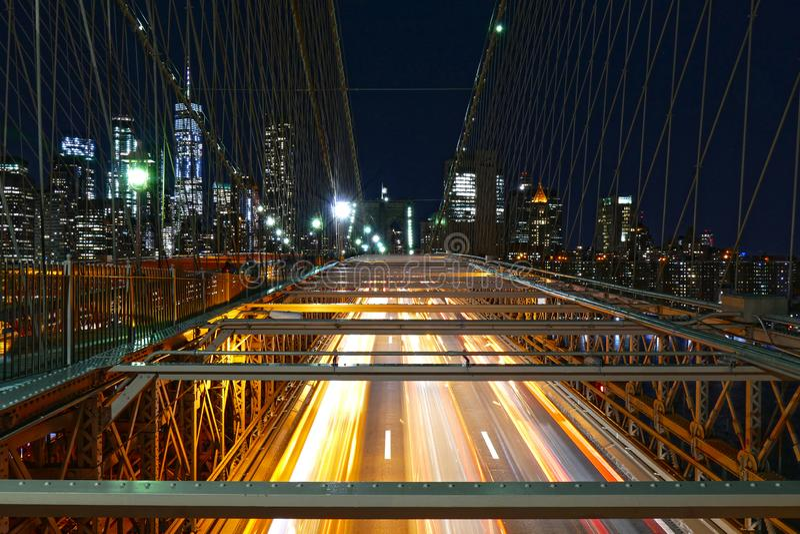 纽约地平线,在布鲁克林大桥的交通在夜、曼哈顿大厦和摩天大楼里 库存照片