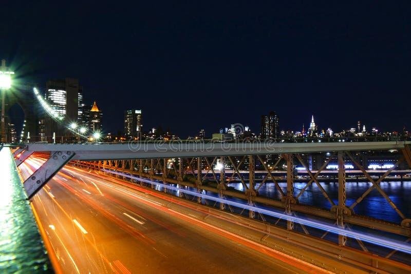 纽约地平线,在布鲁克林大桥的交通在夜、曼哈顿大厦和摩天大楼里 库存图片