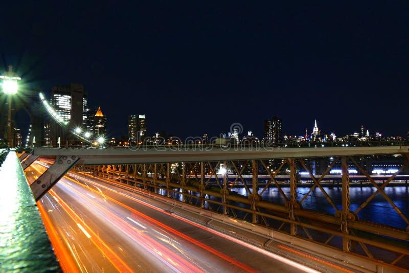 纽约地平线,布鲁克林大桥交通在夜、曼哈顿大厦和摩天大楼里 库存图片