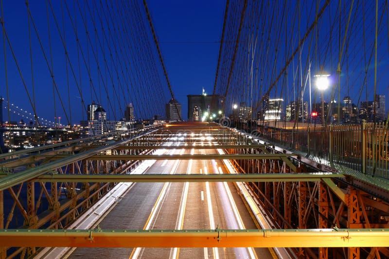 纽约地平线,布鲁克林大桥交通在夜、曼哈顿大厦和摩天大楼里 库存照片