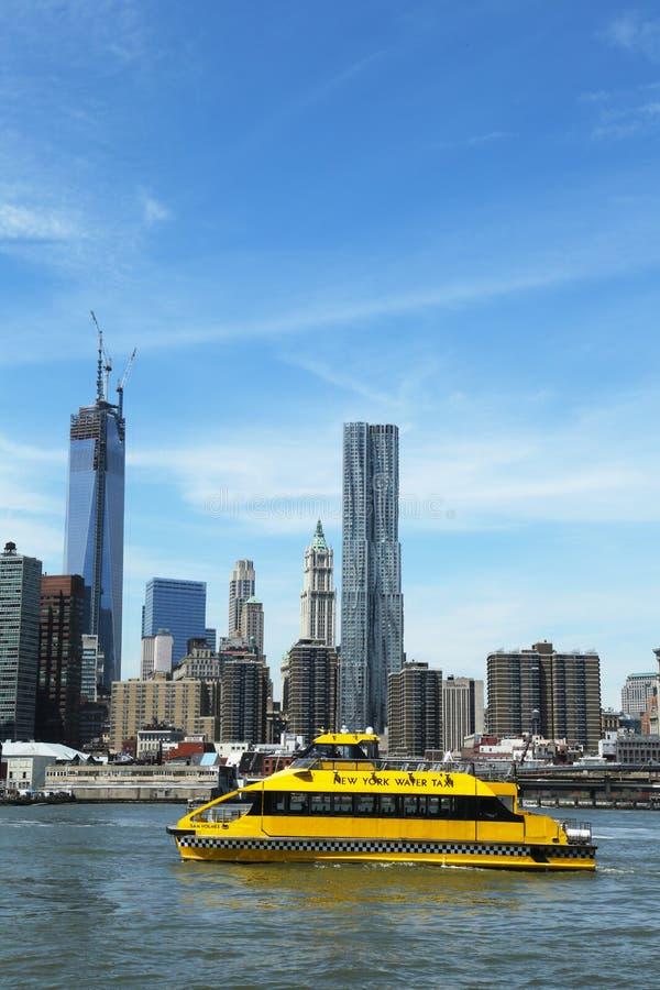 纽约城有自由塔的水出租汽车和从布鲁克林大桥看的NYC地平线停放 免版税图库摄影