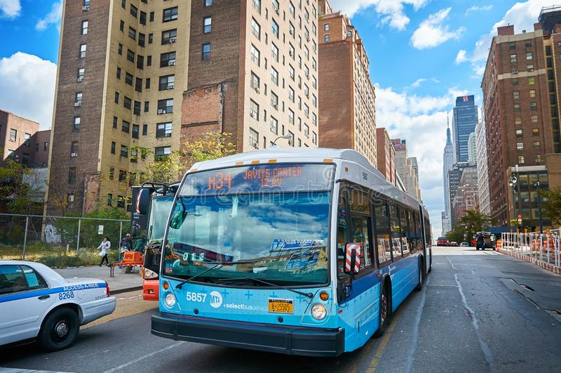纽约,曼哈顿,10月 25日2013年:在NYC公共汽车和汽车的看法在用不同的大厦,backgro的摩天大楼的路 库存图片