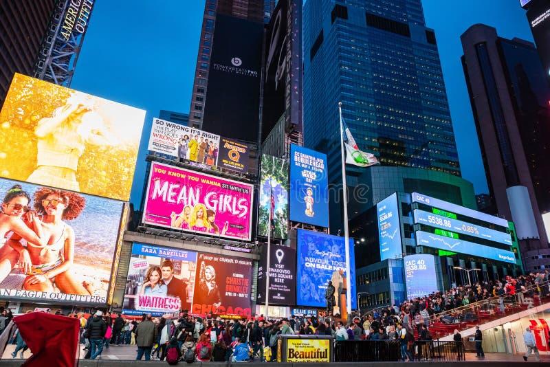 纽约,百老汇在晚上 五颜六色的大等待展示的广告牌和人群 库存照片
