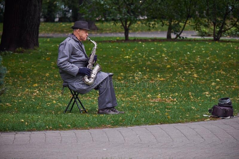 纽约,美国- 2017年7月:一件雨衣和一支帽子plaing的萨克斯管的老人在公园 免版税库存照片