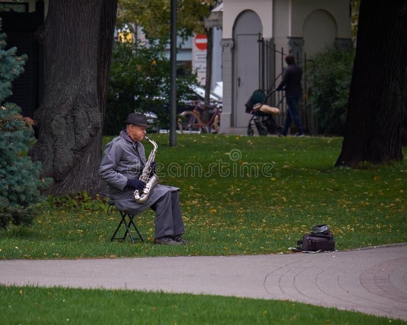 纽约,美国- 2017年7月:一件雨衣和一支帽子plaing的萨克斯管的老人在公园 免版税库存图片