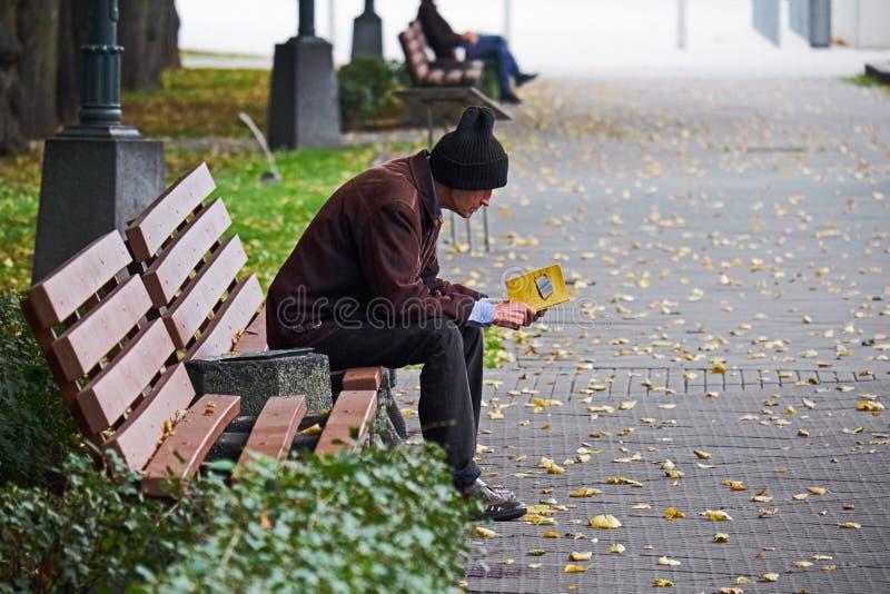 纽约,美国- 2017年7月:棕色夹克和童帽读书的老人一本黄皮书外面在公园 免版税库存图片