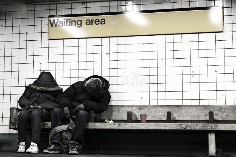 睡觉在NYC地铁等候室的二个人 库存图片
